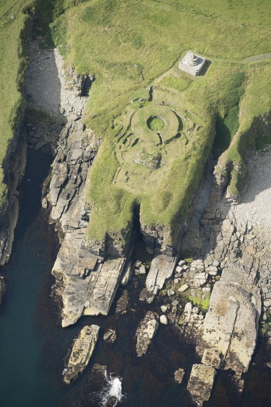 Oblique aerial view of Nybster Broch and Nybster Commemorative Monument, looking WSW.