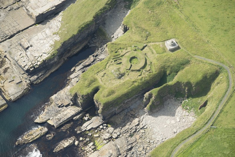 Oblique aerial view of Nybster Broch and Nybster Commemorative Monument, looking SSW.