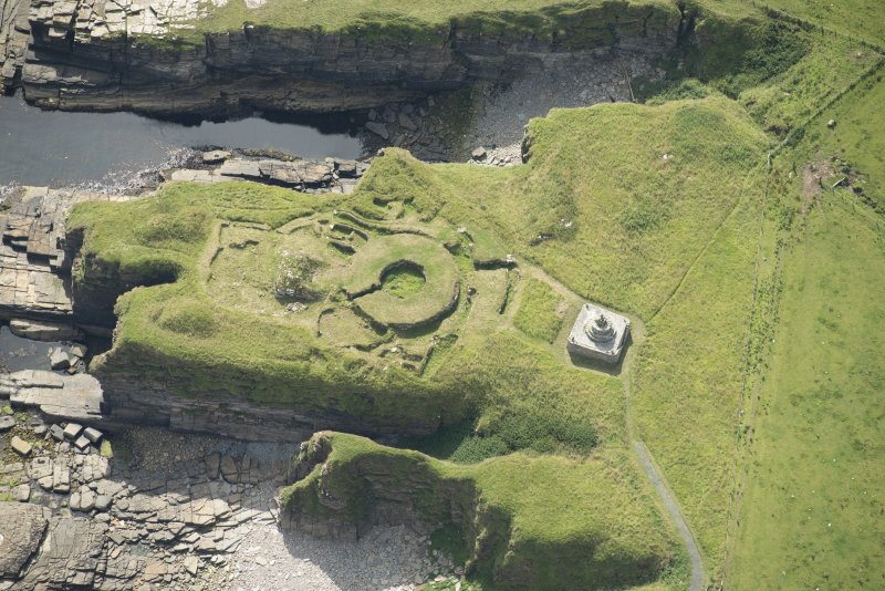 Oblique aerial view of Nybster Broch and Nybster Commemorative Monument, looking SSE.