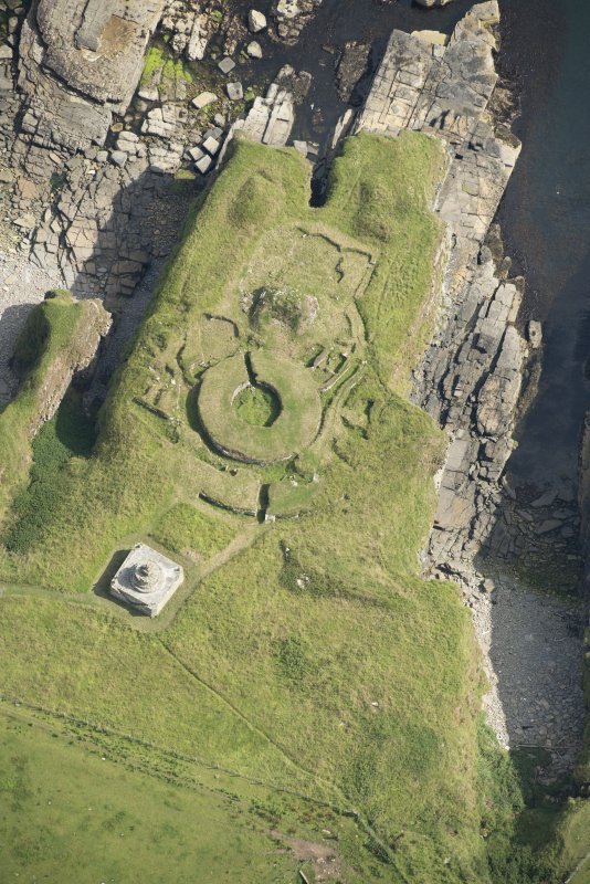 Oblique aerial view of Nybster Broch and Nybster Commemorative Monument, looking NE.