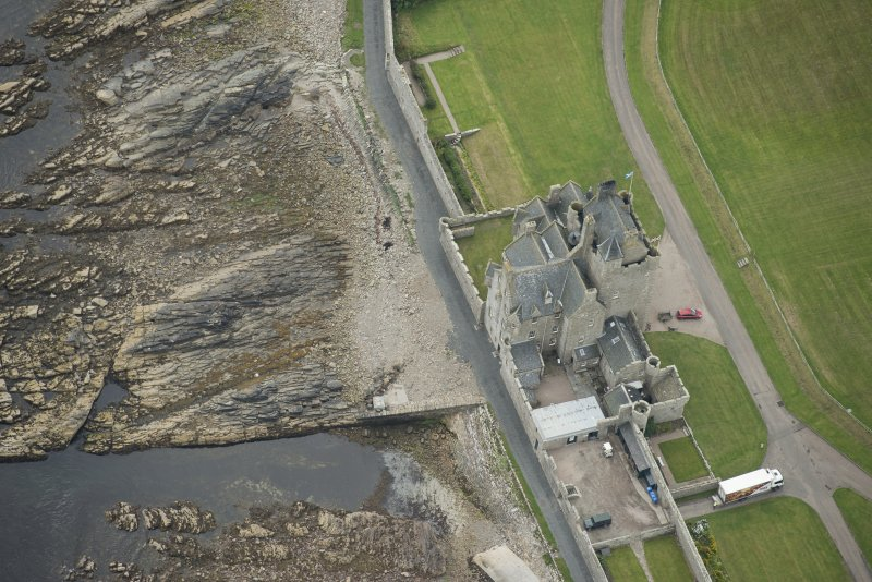 Oblique aerial view of Ackergill Tower and walled gardens, looking SE.