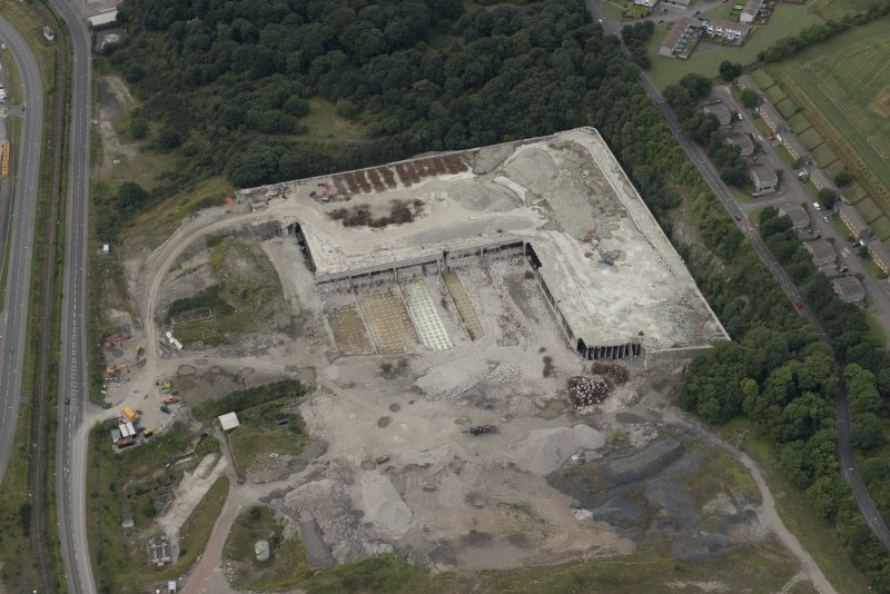 Oblique aerial view of the demolition of the oil storage tanks at Rosyth, looking W.