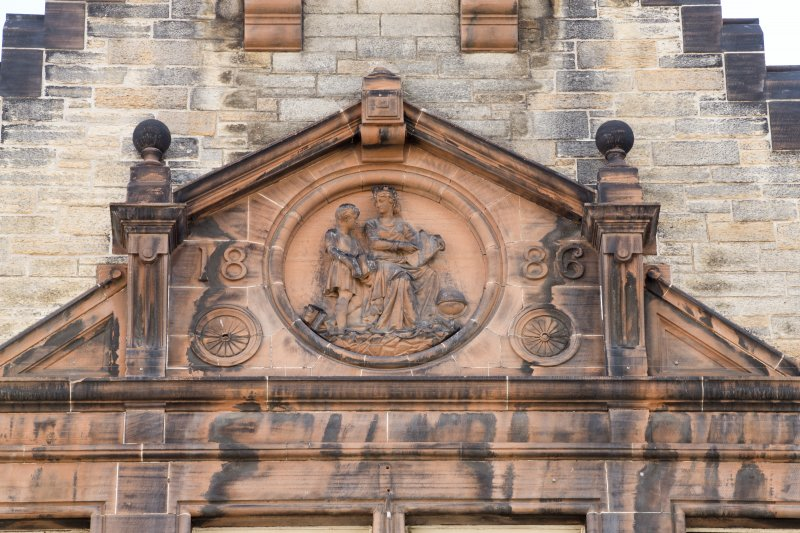 Detail of carved pediment with date '1886' in gable on front elevation of Milton House School, 86 Canongate, Edinburgh.
