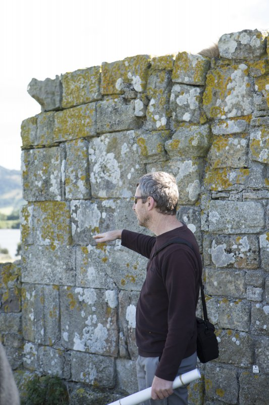 Piers Dixon explaining features of outside of west wall of priory church