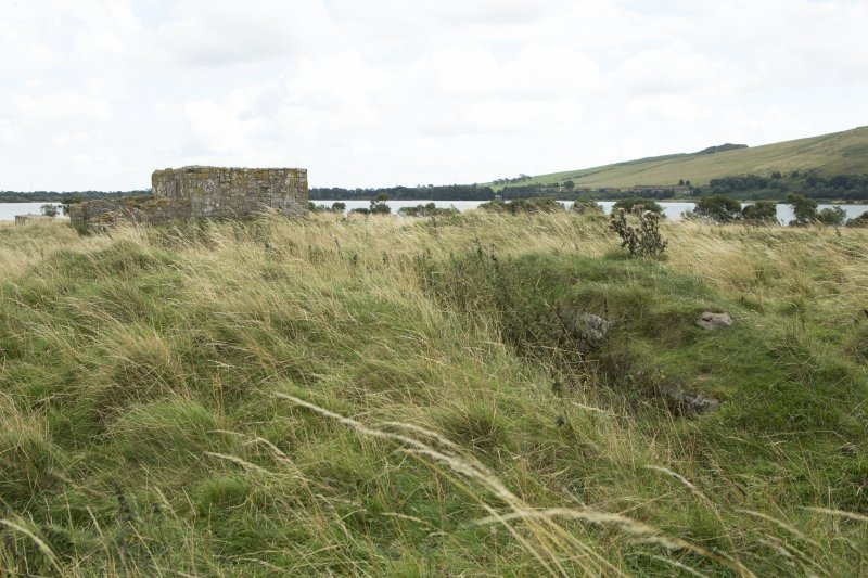 Walling of convent building with priory church in background, view from west
