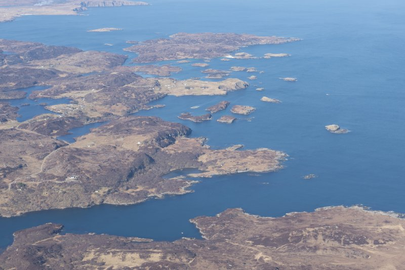 General oblique aerial view of Eddrachillis Bay centred on Eilean an Achaidh and the site of the Drumbeg wreck, looking SW.