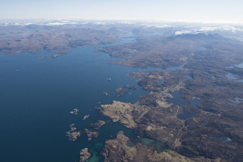 General oblique aerial view of Eddrachillis Bay centred on Eilean an Achaidh and the site of the Drumbeg wreck with Quinag beyond, looking E.