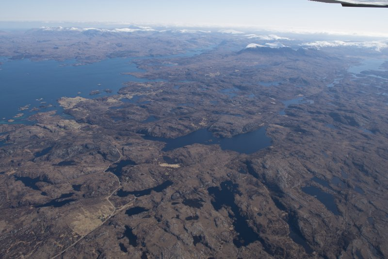 General oblique aerial view of Loch Poll, with Eddrachillis Bay,Eilean an Achaidh, the site of the Drumbeg wreck and Quinag beyond, looking E.