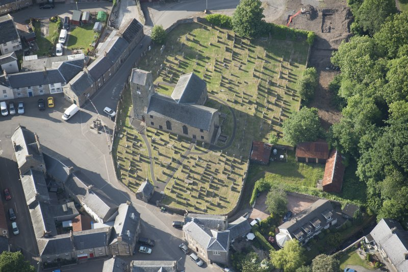 Oblique aerial view of St Serf's Church with the Glasgow University excavations on the edge of the churchyard, looking NNW.