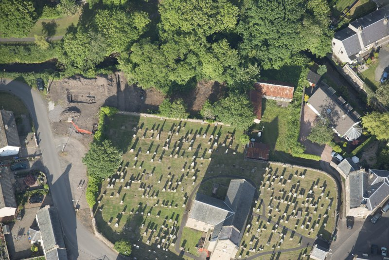 Oblique aerial view of the Glasgow University excavations on the edge of the churchyard, looking ENE.