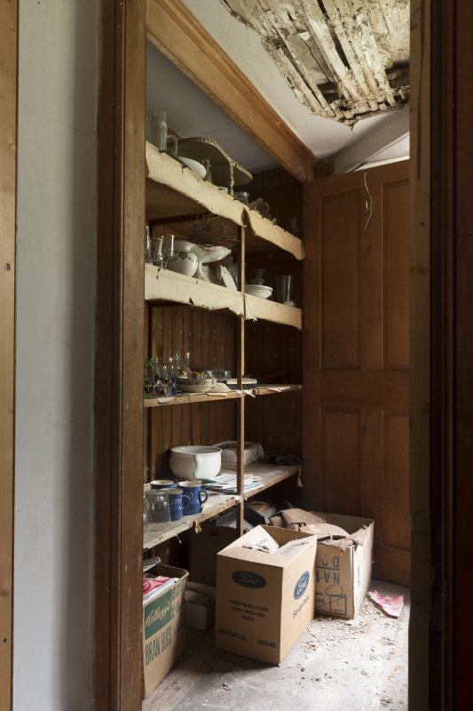 General view of cupboard on stairs showing shelves.