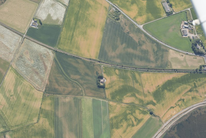 Oblique aerial view of the cropmarks of the palisaded enclosures, the pits, round houses and other cropmarking, looking SE.
