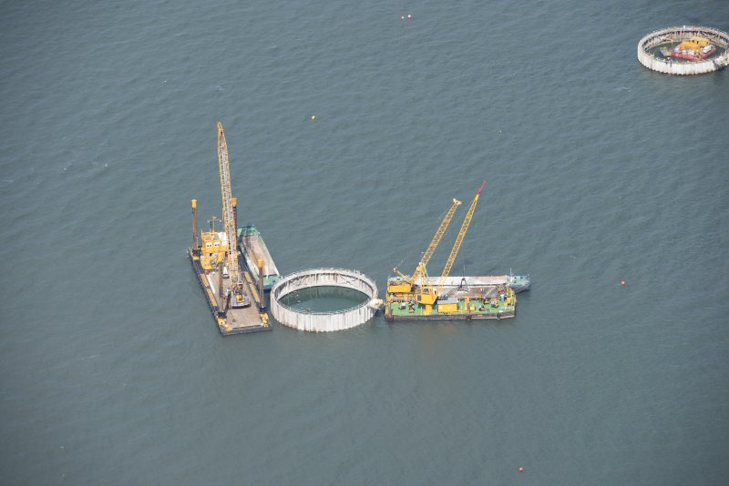 Oblique aerial view of the bridge supports under construction, looking NE.