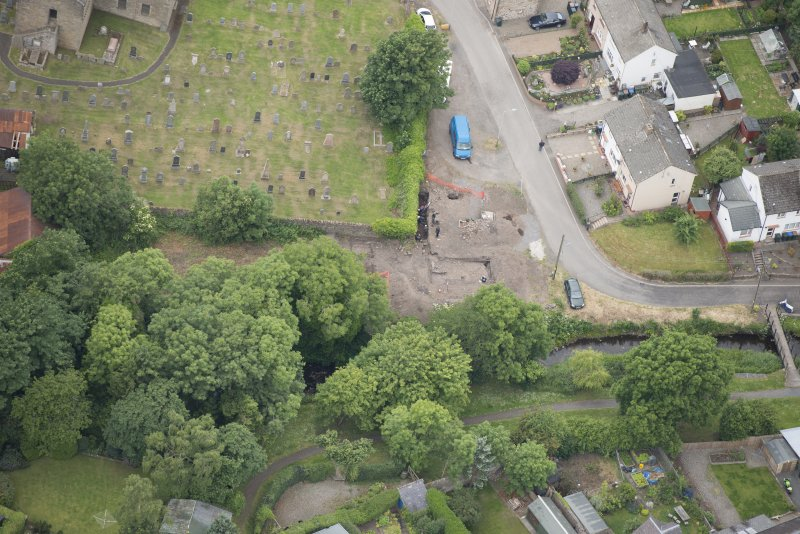 Oblique aerial view centred on the Glasgow University excavations on the edge of the churchyard, looking W.