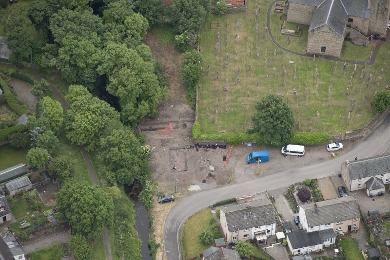 Oblique aerial view centred on the Glasgow University excavations on the edge of the churchyard, looking S.