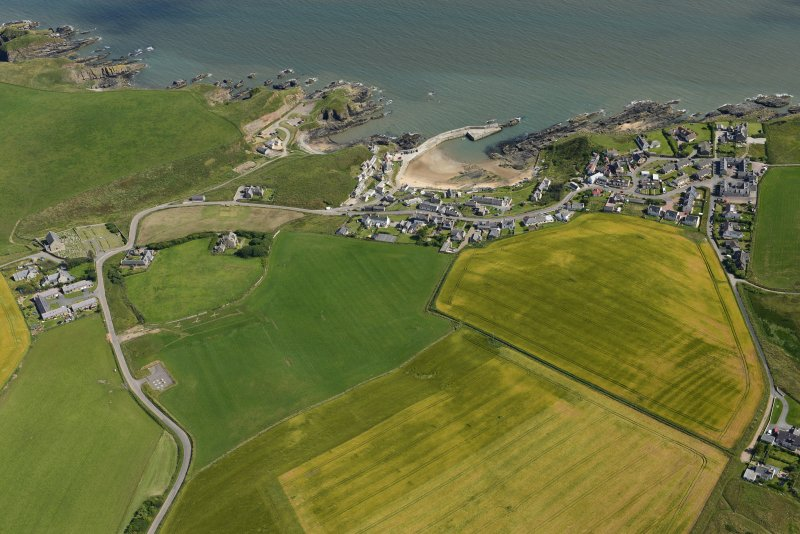 General oblique aerial view centred on Collieston with the cropmarks of the rig adjacent, looking SE.
