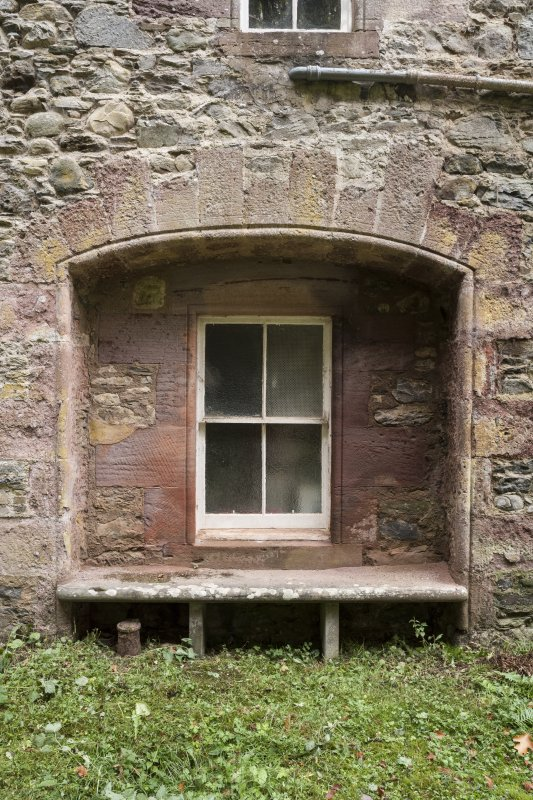Detail of archway and window with stone seat.