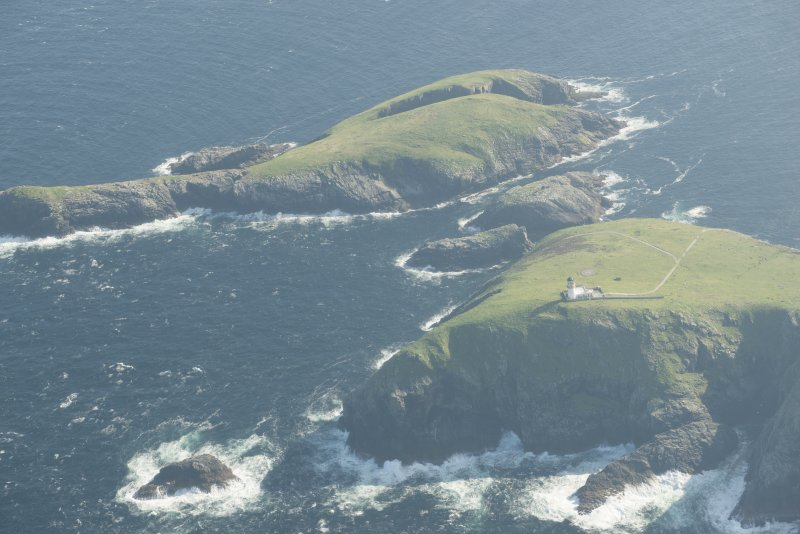 Oblique aerial view of the Flannan Isles, with the lighthouse on Eilean Mor in the foreground and Eilean Tighe beyond, looking to the SSW.