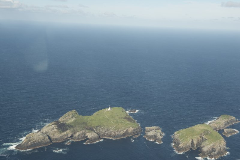 General oblique aerial view of the Flannan Isles, with the lighthouse on Eilean Mor to the left and Eilean Tighe to the right, looking to the NE.