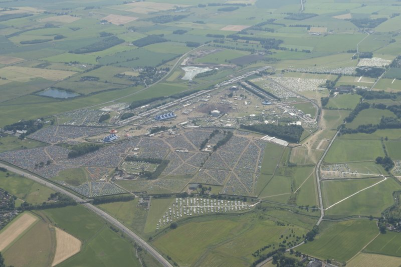 General oblique aerial view centred on the T in the Park festival at Balado, looking SW.