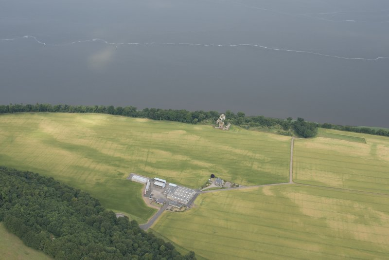 Oblique aerial view of Ballinbreich Castle and farmstead, with the cropmarked field in between, looking N.