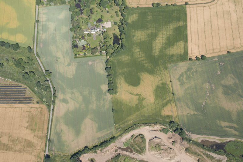Oblique aerial view of the cropmarks of the rig, houses and pits with Woodhill House adjacent, looking NW.