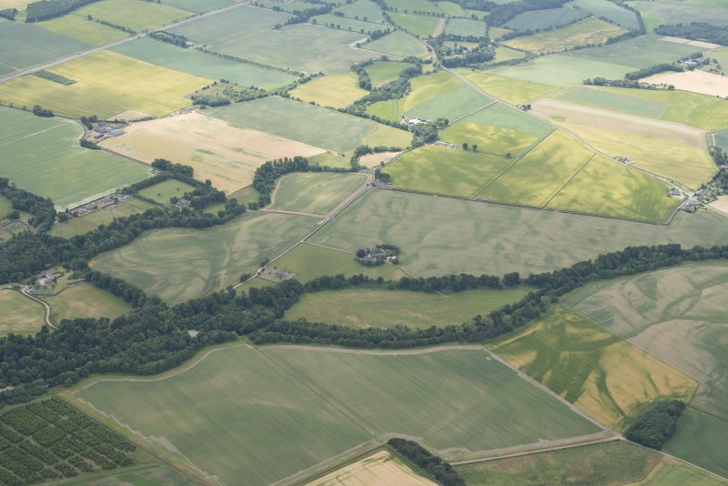 General oblique aerial view centred on the cropmarks of the unenclosed settlement, ring ditches, pits and rig with Stracathro Roman Fort and Temporary Camp adjacent at Smiddyhill, looking to the SSW.