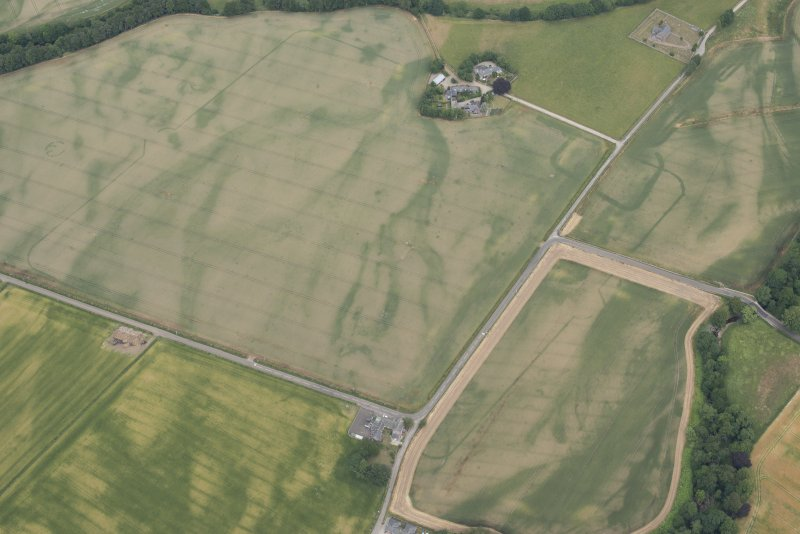 Oblique aerial view centred on the cropmarks of Stracathro Roman temporary camp, looking NE.