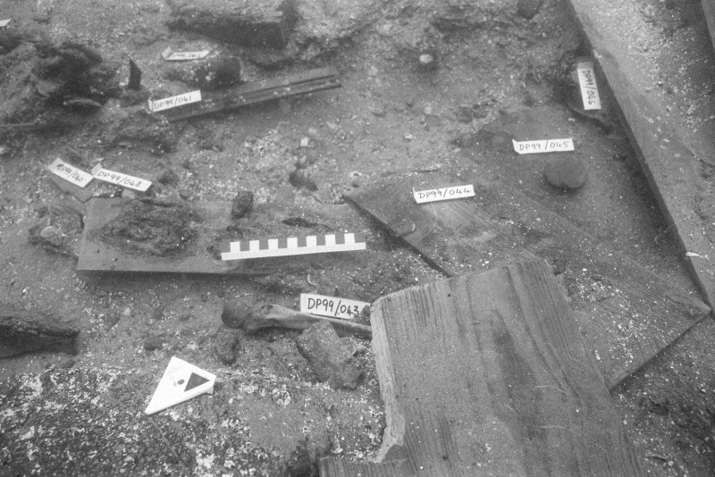 Labelled wooden finds prepared for recording, packing, and bringing to the surface. Scale 15 centimetres. (Colin Martin)