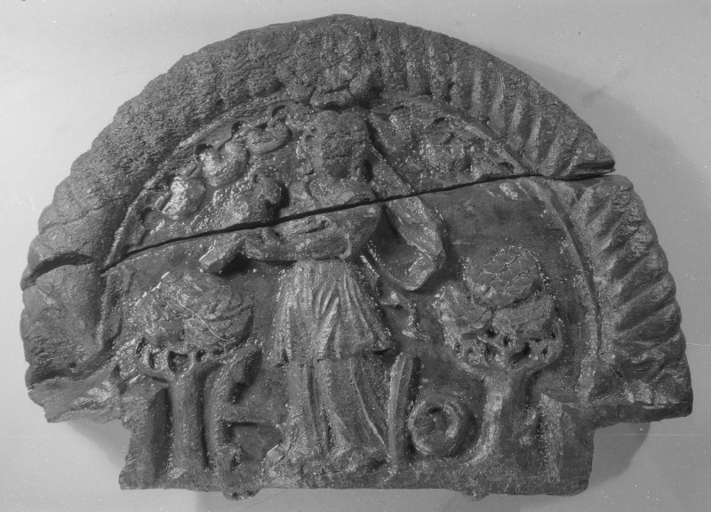 A carving of the virtue of Hope (DP00/081, 083). It is a semicircular panel which would have formed a central feature of the decorated stern. Hope is depicted as a draped female figure holding one of her attributes, a crow. The other attributes are two oak trees, signifying strength, and an anchor—anchora spei—the anchor of hope. (Colin Martin)