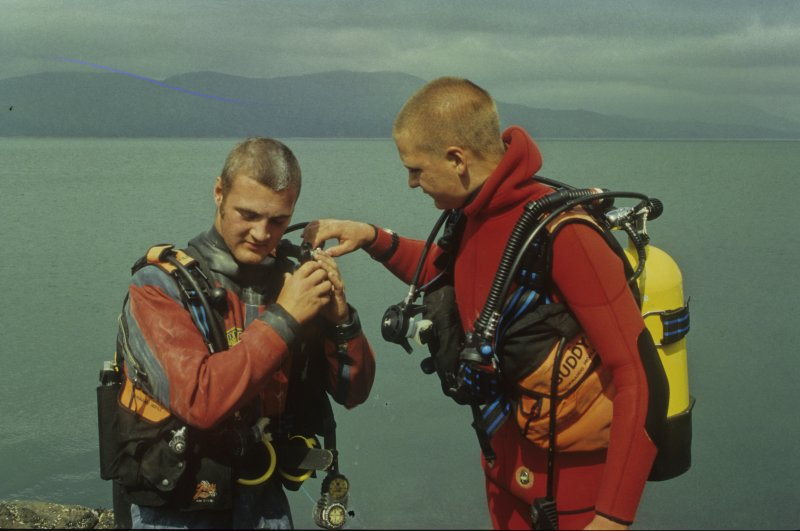 Peter Martin (left) and Edward Martin check each other's equipment in preparation for a shore-based SCUBA dive. (Colin Martin)