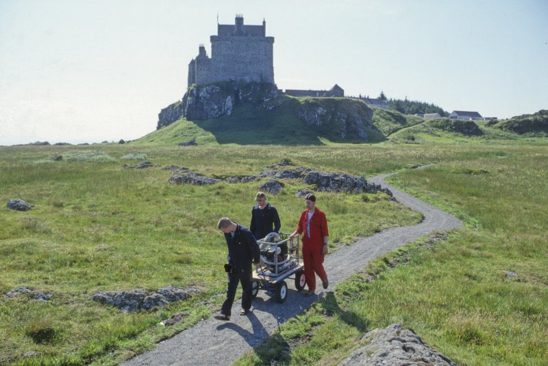 A long trail a-winding. Edward and Peter Martin, and Neil Dobson, transport the hookah compressor from the project base (tucked behind the buildings to the far right of the castle) to the shore base. The path was laid by the Macleans to assist our access to the shore, and now accommodates visitors who come to look at the site and the information plaque above it. (Colin Martin)