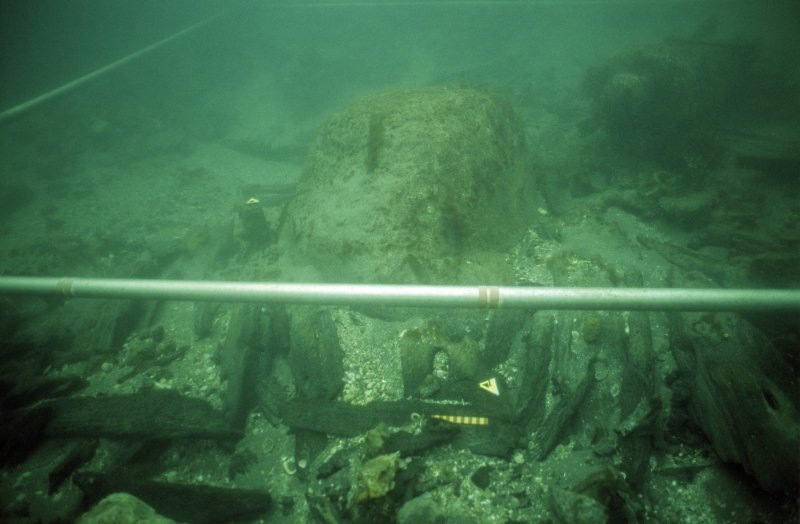 The displaced timbers surrounding this large rock are fragmented pieces of the hull, showing that the rock was in this position when the sinking vessel struck it, causing major damage to the port bow quarter. No timbers extend under the rock. Gun 6 is visible on the upper right. Metre graduations are visible on the grid-pole. (Colin Martin)