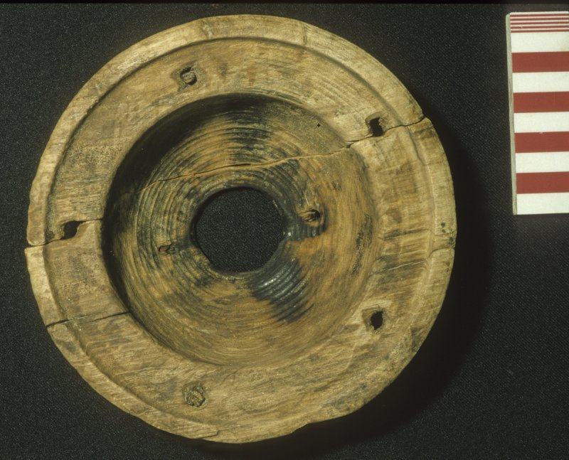 Underside of the upper part of a wooden lantern (DP99/002). Note the burn marks and the holes for five uprights. Scale 10 centimetres. (Colin Martin)