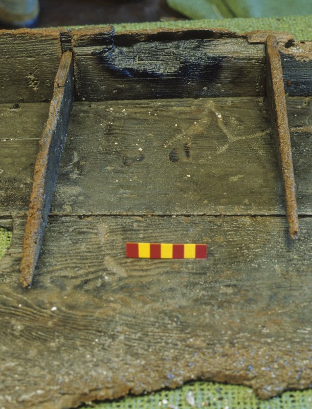 The binnacle (DP96/004) – detail of burn marks in the central compartment. Scale 10 centimetres. (Colin Martin)