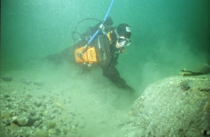 Excavating by hand under water. A longitudinal trench 30cm deep is created by hand fanning, spoil being pulled to the excavator's rear. The natural angle of repose—here around 45º—creates a run ...