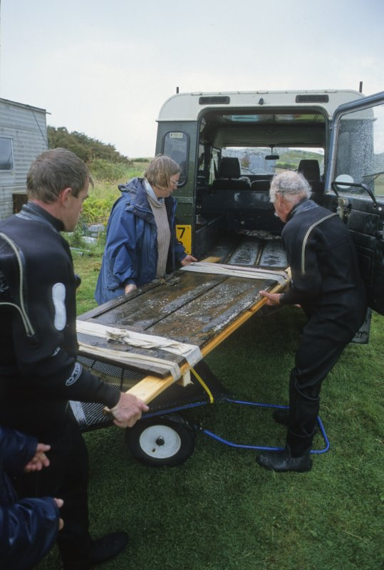 Graham Scott (left), Dr Paula Martin and Dr Colin Martin carefully load a wooden panelled door (DP00/146) on a lifting-frame to which it is secured with bandages into a Land Rover for transport to wet holding-tank. Once inside it will be covered with wet towels. (Edward Martin)