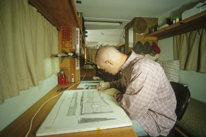 Peter Martin preparing finds drawings in the headquarters caravan. (Colin Martin)