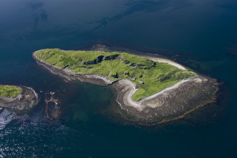 Aerial photograph of Sheep Island from the SE. The three kilns and associated buildings are clustered round the small bay. On the left is a horseshoe-shaped reef (an Càrn = pile of stones) which appears to have served as a ballast dump. (Colin Martin)