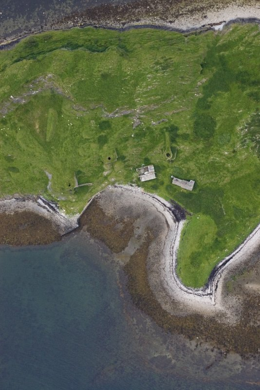 Near-vertical aerial photograph of Sheep Island (Eilean nan Caorach) from the NE. The three kilns and associated buildings are clustered round the bay. A built quay is visible at the top edge of the bay, while a presumably earlier cleared strip runs up the centre of the beach. (Colin Martin)