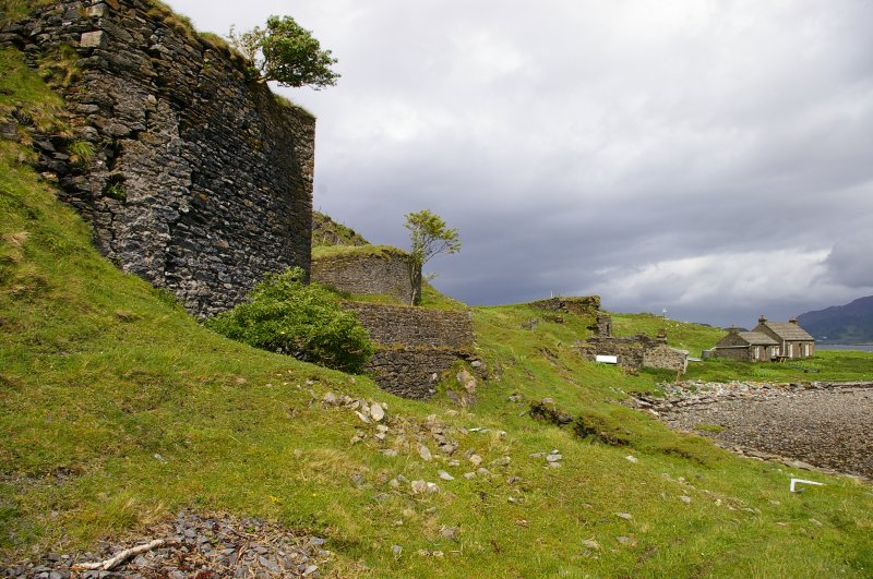 Sheep Island (Eilean nan Caorach). View along the kiln frontages, looking NE. The lime-workers' bothy, now a holiday home, is on the right. Above it, on the skyline, is Kiln 1. Between the bothy and Kiln 1 is a complex of stores and workshops. Kiln 2 is left of centre, with a tree growing out of its top. Kiln 3, with its extension, is at the upper left. (Colin Martin)