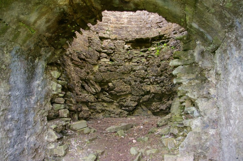 Draw-arch, Kiln 2; view from the broken-down end wall showing the kiln lining on the far side. The lower part is cut from the natural rock, while the upper level is cased in end-laid bricks. (Colin Martin)
