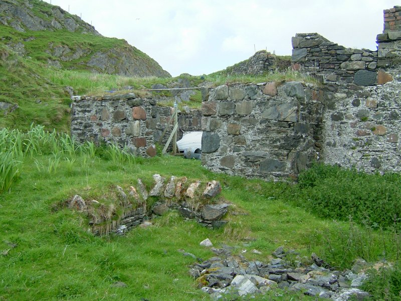 Remains of one of two wells on the island. Behind is the wide entrance to the unroofed enclosure which was probably a coal store. (Paula Martin)