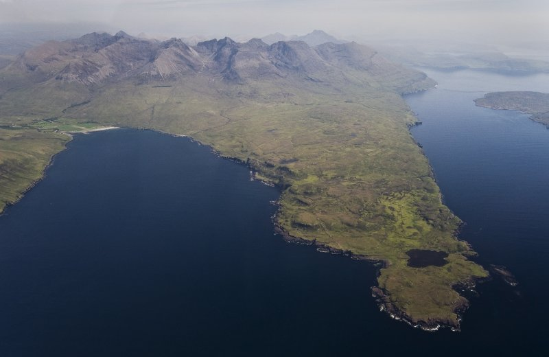 Aerial photograph of the Rubh' an Dùnain peninsula from the W, with the Cuillin Hills rising in the background. Loch na h-Airde is close to the tip of the peninsula. Loch Brittle is on the left, with Glenbrittle at its head. (Edward Martin)