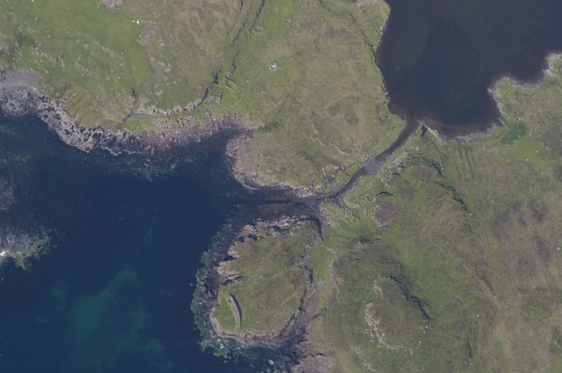 Aerial photograph of the headland fort and canal from the SE. Underwater indications of a stone-built quay can be seen on either side of the canal's entry to the loch. Beyond the canal entrance a basin of deeper water largely clear of weed is visible. (Colin Martin)
