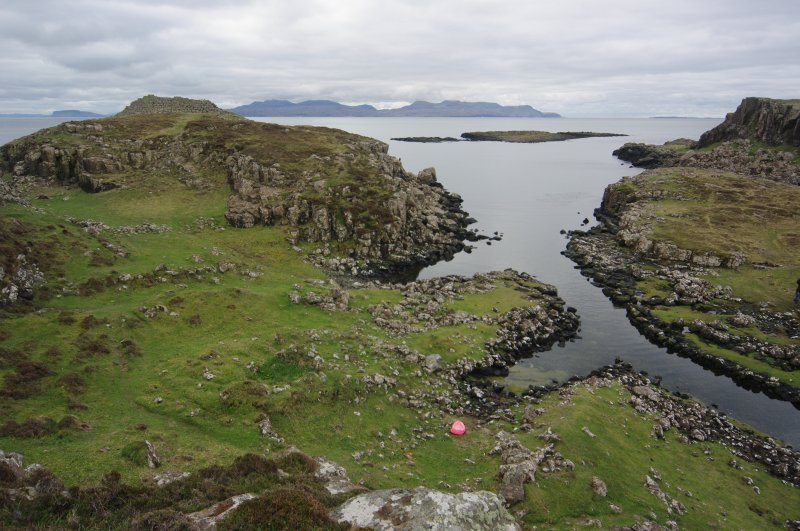 Headland fort (skylined, on left), the two nausts below it, and the canal leading into Loch na h-Airde. The islet of Sgeir Mhòr and the sheltered anchorage lie beyond. Rum is on the horizon, and the  ...