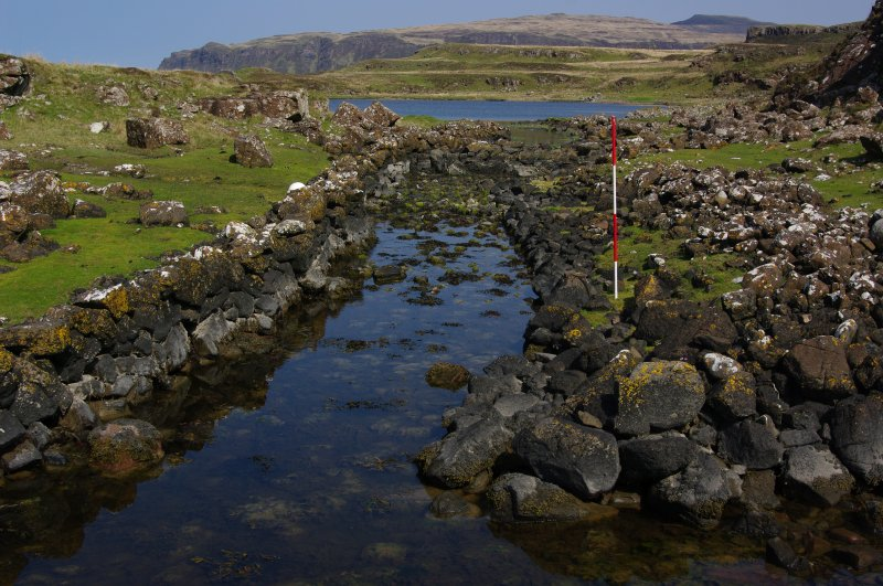 The upper canal leading into Loch na h-Airde, with the blockage part-way along it. The left-hand revetment is relatively intact, but that on the right appears to have been dismantled to its foundations and the stones thrown onto the bank. Tradition asserts that this was done to bring larger vessels into the loch. Scale 2 metres. (Colin Martin)