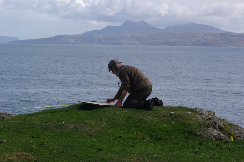 The site was potentially dangerous, and risk assessments were rigorous. Project Director Dr Colin Martin is more secure than he looks as he records details of the headland fort. (Paula Martin)