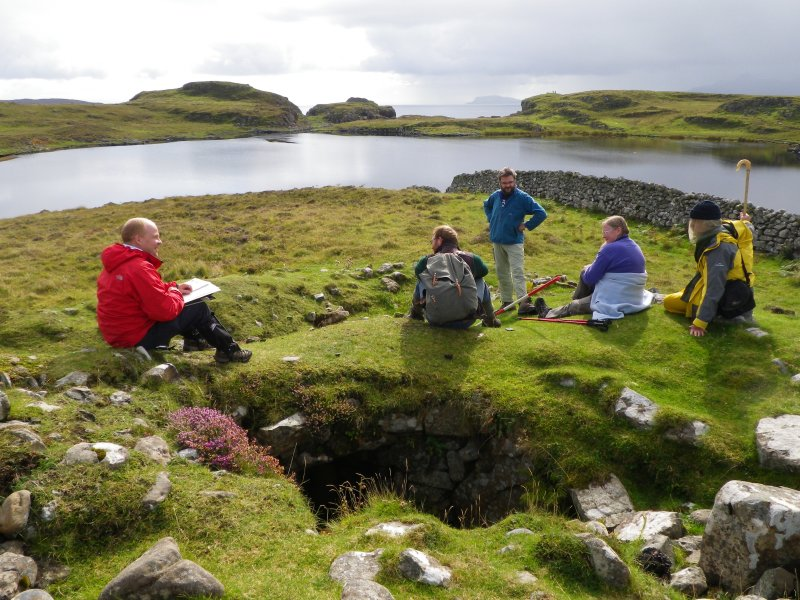 This site has elicited much interest and discussion from heritage agencies and others. Here, seated on the remains of a Neolithic chambered cairn overlooking Loch na h-Airde in September 2013, an informal international seminar is taking place. From left, Philip Robertson (Historic Scotland), George Geddes (Royal Commission on the Ancient and Historic Monuments of Scotland), Edward Martin (archaeological photographer), and Dr Ian MacLeod (Western Australian Museum). Behind the camera is Dr Colin Martin (University of St Andrews). (Colin Martin)