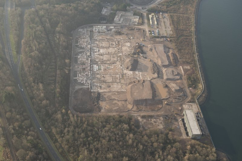 Oblique aerial view of the remains of Inverkip power station during post-demolition clearance, looking to the WSW.